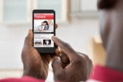 Close-up Of African Young Man Reading News On Smartphone