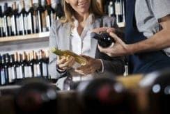 Salesman Assisting Female Customer In Choosing Wine
