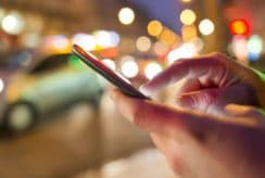 Man using his Mobile Phone in the street, night light bokeh Background